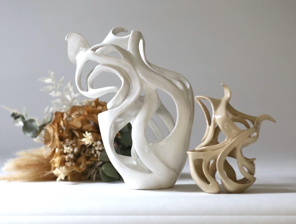 Sculpture céramique contemporaine vue de dos avec son déhanché julie Espiau émaillée couleur ficelle avec la sculpture rose des sables et un bouquet de fleurs séchés au second plan
