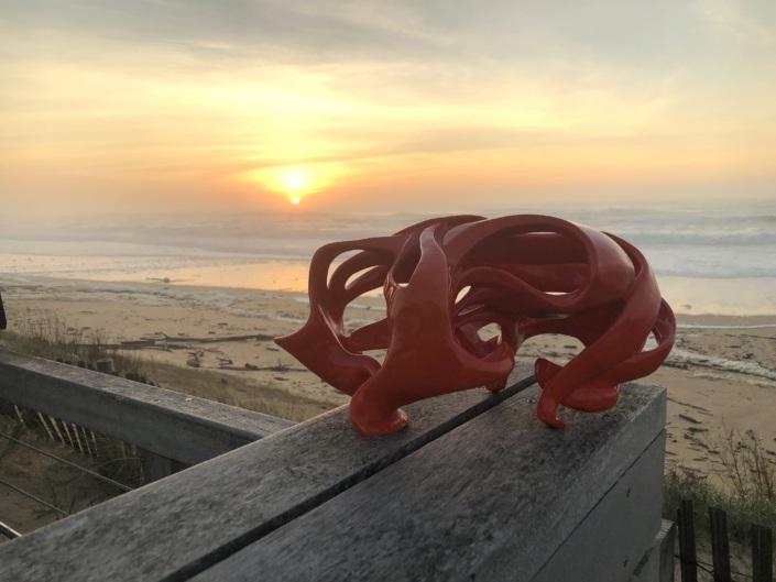 Sculpture céramique Julie Espiau. Photographie prise à la plage d'Ondres dans les landes au coucher de soleil sur un banc en bois.